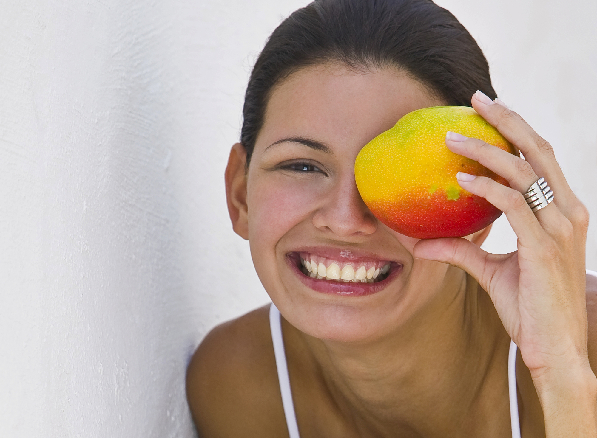 Woman holding mango in front of face outdoors, smiling, portrait