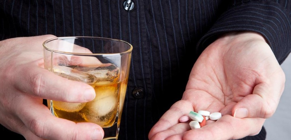 hands-holding-glass-of-whiskey-and-pills1-997x480