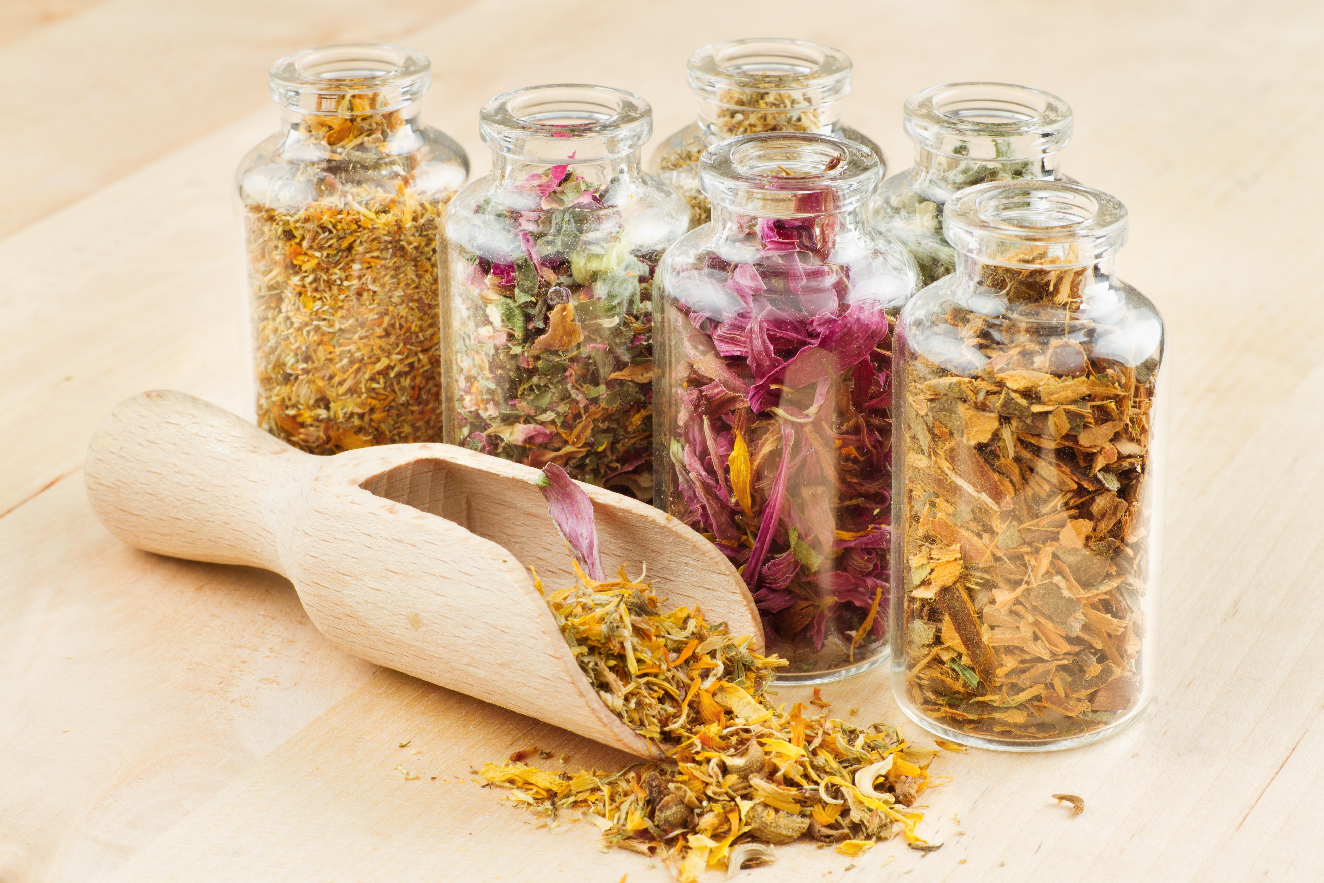 healing herbs in glass bottles and wooden scoop, herbal medicine